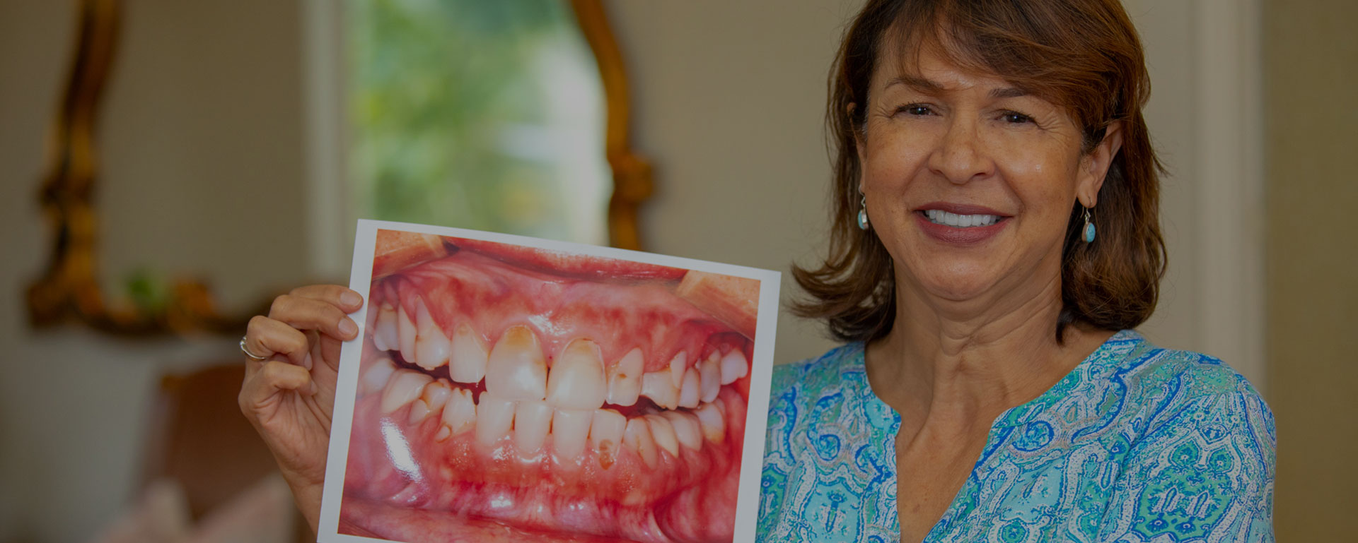 A patient holding up a photo of her teeth